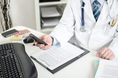Doktor som rymmer en telefon Royaltyfri Fotografi
