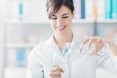Doktor som rymmer ett exponeringsglas av vatten och en flaska Arkivfoton