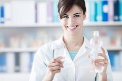 Doktor som rymmer ett exponeringsglas av vatten och en flaska Arkivfoto