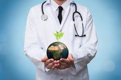 Doktor som rymmer ett planetjordjordklot i hans händer Miljö och sunt begrepp för global ekologi royaltyfri foto