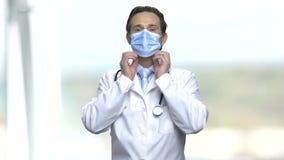 Doktor som sätter på blå medicinsk maskering stock video