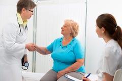 Doktor som skakar händer med patienten Arkivbild