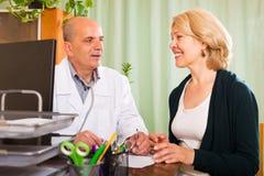 Doktor som talar med den mogna kvinnliga patienten Arkivbild