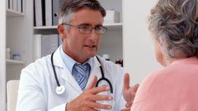 Doktor som talar med hans patient på skrivbordet stock video