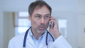 Doktor som talar på telefonen som deltar i påringning stock video
