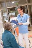 Doktor som talar till den höga patienten i sjukhus fotografering för bildbyråer
