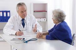 Doktor som talar till hans kvinnliga höga patient royaltyfri fotografi