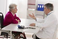 Doktor som talar till hans rörelsehindrade höga patient arkivfoto