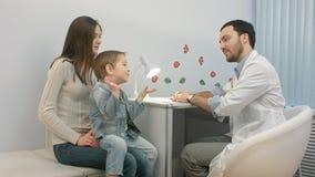 Doktor som talar till unga barnet och modern arkivfoton