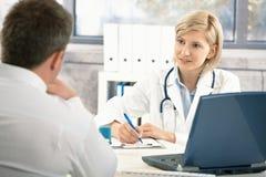 Doktor som tar anmärkningar om tålmodig Arkivbilder
