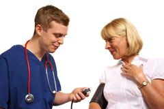 Doktor som tar blodtryck av tålmodign royaltyfri bild