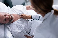 Doktor som tar hjärtslag av den sjuka patienten royaltyfri bild