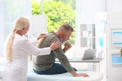 Doktor som undersöker den hostande mogna mannen fotografering för bildbyråer