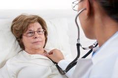 doktor som undersöker den patient pensionären Arkivbild