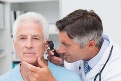 Doktor som undersöker det höga patientörat med otoscopen Arkivbilder