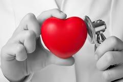 Doktor som undersöker en hjärta Fotografering för Bildbyråer