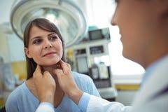 Doktor som undersöker en kvinnlig patienthals royaltyfri foto