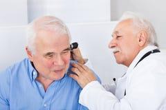 Doktor som undersöker hög mans öra med otoscopen royaltyfri foto