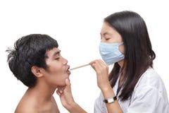 doktor som undersöker patient spatelhals w Royaltyfri Bild