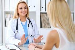 Doktor som uppmuntrar hennes kvinnliga patient Medicin-, hjälp- och hälsovårdbegrepp royaltyfri fotografi