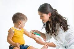 Doktor som vaccinerar barnet Arkivfoto