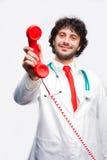 Doktor som visar en klassisk telefonreciver royaltyfri fotografi