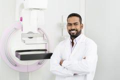 Doktor Standing Arms Crossed vid Mammographymaskinen Royaltyfri Bild