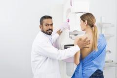 Doktor Standing Assisting Patient som genomgår Mammogramröntgenstrålen Tes Royaltyfri Foto