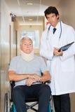 Doktor Standing By Patient auf Rollstuhl Stockbilder