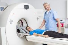 Doktor Standing By Patient som ligger på MRI-maskinen royaltyfria bilder