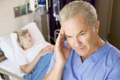 Doktor Standing In Patients Room Lizenzfreie Stockfotografie