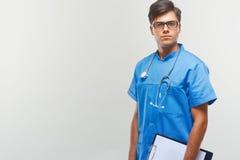 Doktor With Stethoscope Around hans hals mot Grey Background royaltyfri foto