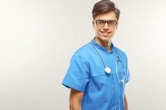 Doktor With Stethoscope Around hans hals mot Grey Background royaltyfri bild