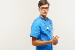Doktor With Stethoscope Around hans hals mot Grey Background fotografering för bildbyråer