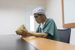 Doktor studiert menschliches Schädelmodell die Bibliothek Stockfotografie