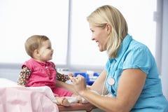 Doktor In Surgery Examining behandla som ett barn flickan Royaltyfri Bild