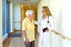 Doktor Talking zu den älteren Personen am Krankenhaus-Korridor Stockfotografie