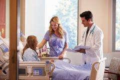 Doktor Talks To Mother med den tonårs- dottern i sjukhus arkivbild