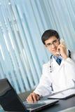 Doktor am Telefon im Büro Lizenzfreies Stockfoto