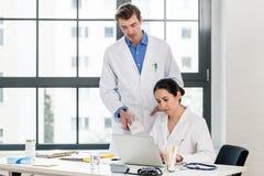 Doktor und Apotheker, die Informationen über einen Laptop in einem Krankenhaus überprüfen Stockbild