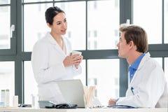 Doktor und Apotheker, die Informationen über einen Laptop in einem Krankenhaus überprüfen Stockfoto