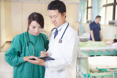 Doktor und Assistent besprechen Situation stockfoto