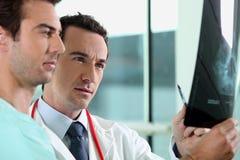 Doktor und Assistent mit Röntgenstrahl lizenzfreies stockbild