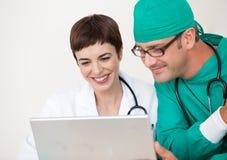 Doktor und Chirurg, die einen Laptop betrachten lizenzfreies stockfoto