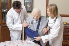 Doktor und die Krankenschwesterhilfe die alte Frau vom Stuhl aufstehen Eine alte Frau mit einer Hand in einem Riemen stockbild