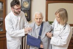 Doktor und die Krankenschwesterhilfe die alte Frau vom Stuhl aufstehen Eine alte Frau mit einer Hand in einem Riemen stockfoto