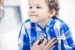 Doktor und geduldiges Kind Arzt, der wenig Jungen ?berpr?ft Regelm??iger medizinischer Besuch in der Klinik Medizin und Gesundhei lizenzfreie stockbilder