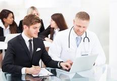 Doktor und Geschäftsmann, die über Laptop sich besprechen Lizenzfreies Stockfoto