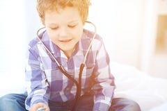 Doktor- und Kinderpatient Spiel des kleinen Jungen mit Stethoskop, während Arzt mit ihm sich verständigen hildren ` s Therapie un Stockbilder