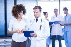 Doktor und Kollege, die ärztlichen Attest betrachten lizenzfreie stockfotografie
